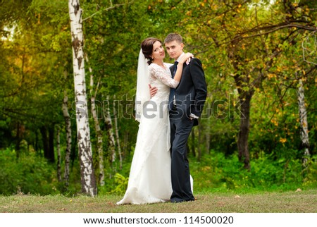 A beautiful bride adjusts her grooms suit as they stroll through the gardens - stock photo