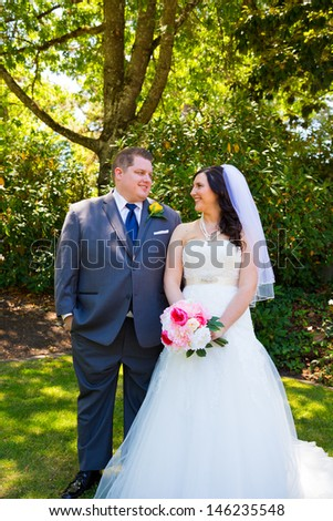 A beautiful bride and groom pose for portraits on their wedding day at a park outdoors.