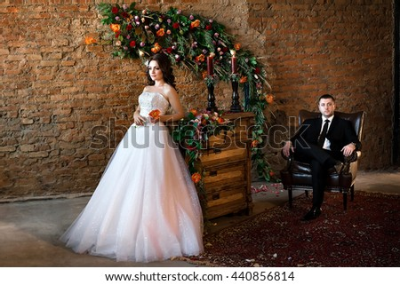 A beautiful bride standing full length in a nice white dress, her groom sitting in a leather chair behind her - stock photo