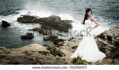 A beautiful bride standing on the coast - stock photo