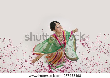 A beautiful bride surrounded by rose petals - stock photo
