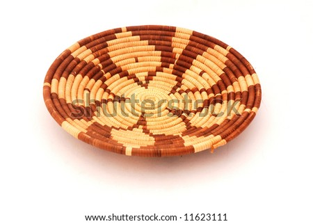 A beautiful brownish African bowl handmade from natural material from South Africa as holiday souvenir. Image isolated on white background