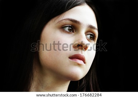 A beautiful brunette girl face on a black background - stock photo