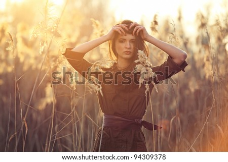 A beautiful brunette girl posing in a field on autumn.Art photo. - stock photo
