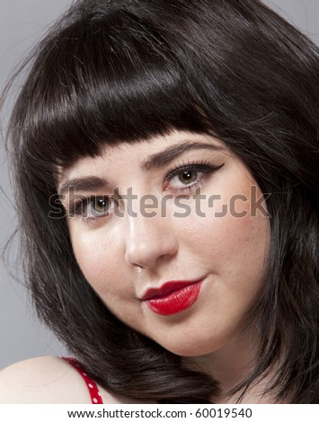 A beautiful brunette in retro clothes and with 50s style  makeup - stock photo