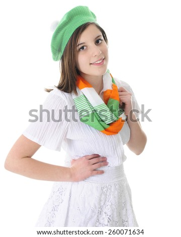 A beautiful brunette teen in white skirt and blouse, adorned with an infinity scarf and hat in green, white and orange.  On a white background. - stock photo