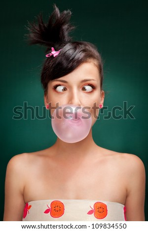 a beautiful brunette with squint eyed blowing a bubblegum on a green background - stock photo