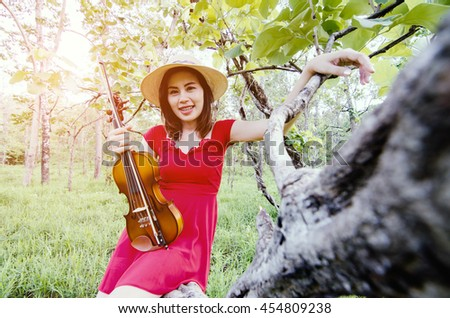 A beautiful brunette woman in a forest with a violin.