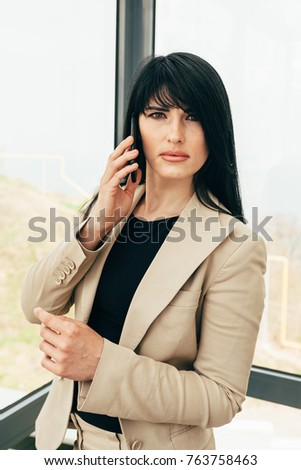 a beautiful business girl in a beige strict suit are standing in a room with picturesque views and adjusts fher jacket her hand and rings