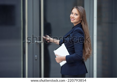 A beautiful business woman entering the office - stock photo