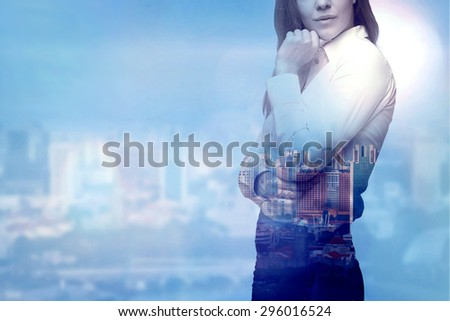 A beautiful business woman is thinking about business solutions. City view in blur as a background. - stock photo