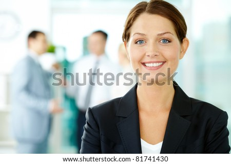 A beautiful businesswoman looking at camera in working environment - stock photo