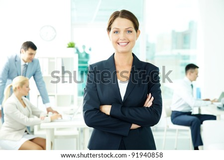 A beautiful businesswoman looking at camera with working people on background