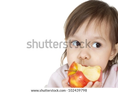 A beautiful Caucasian baby is eating an apple on a white background