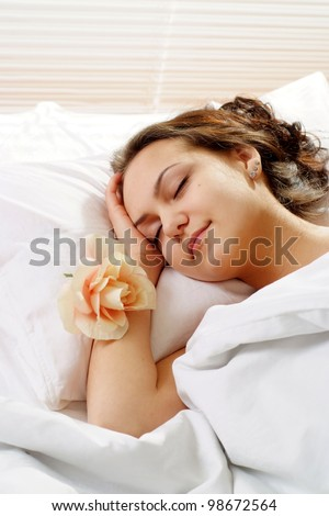 A beautiful caucasian girl with a flower in a bed on a light background