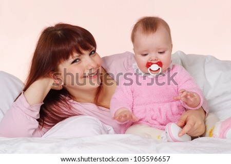 A beautiful Caucasian mama with her daughter lying in bed on a light background