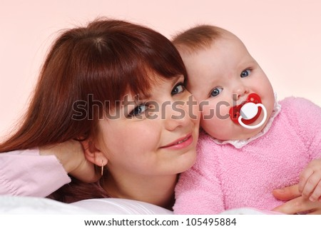 A beautiful Caucasian mom with her daughter lying in bed on a light background
