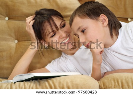 A beautiful Caucasian mother and a charming son lying on a brown background