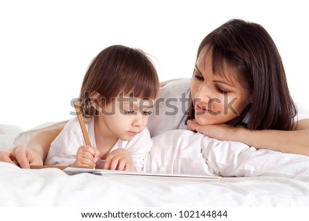 A beautiful Caucasian mum with her daughter lying on the bed with a pencil