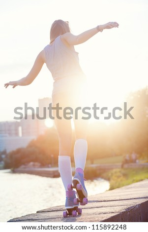 A beautiful caucasian roller skater woman during the sunset, outdoor - stock photo
