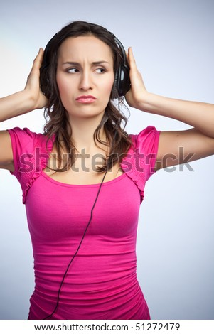A beautiful caucasian woman listening to music on headphones - stock photo