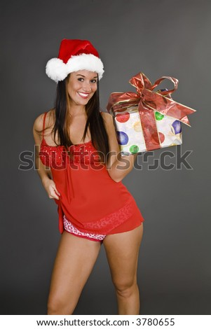 A beautiful caucasian woman with brunette hair dresses in sexy Santa lingerie and holding a Christmas gift isolated on a gray background