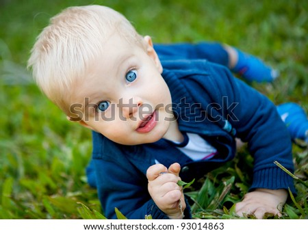 A beautiful cheeky baby boy on the grass making eye contact with the camera - stock photo