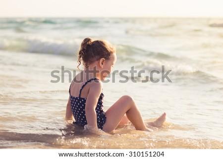A beautiful child playing on sunset beach, toned image - stock photo