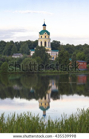 A beautiful Church near the water. Evening. The Church of St. Nicholas from the 19th century in the Grebnevo estate in the Moscow region. - stock photo