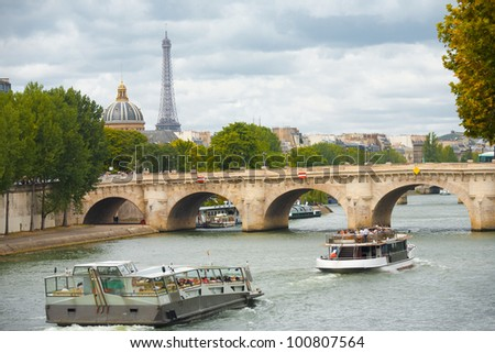 A beautiful cityscape including the Eiffel Tower in the distance with cruise ships passing the pont neuf on the Seine River in Paris, France - stock photo