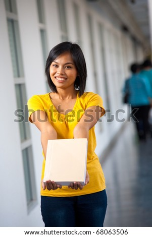 A beautiful college student shows a blank book where text can be inserted.  20s female Asian Thai model of Chinese descent. - stock photo