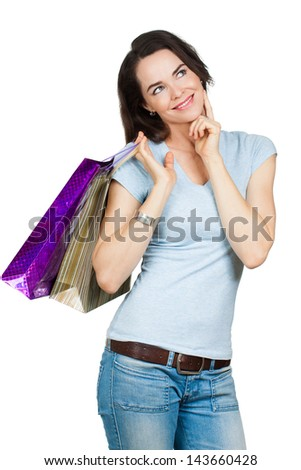 A beautiful contemplative woman holding shopping bags and looking at copy-space. Isolated on white. - stock photo