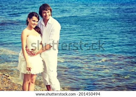 A beautiful couple is posing on the beach - stock photo