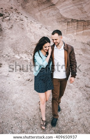 a beautiful couple on the background of the sandy cliff. girl in a blue dress hugging a guy in the background of a mountain
