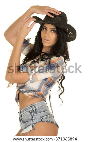 A beautiful cowgirl standing in small shorts with her hands on her cowboy hat. - stock photo