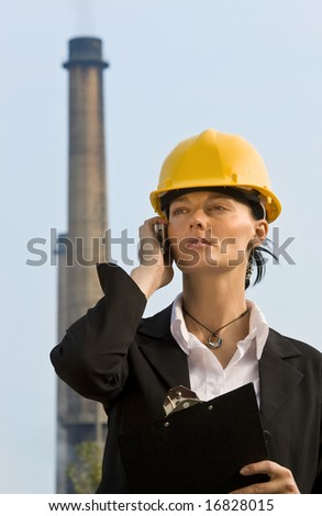 A beautiful dark haired woman wearing a hard hat and talking on her mobile phone while standing in front of a factory and its chimneys - stock photo