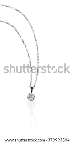A beautiful diamond and white gold round brilliant solitaire pendant dangles from a chain. Fine Jewelry necklace isolated on a white background with shadow and reflection - stock photo
