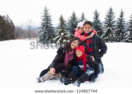 A beautiful East Indian parents play with her children in the snow.