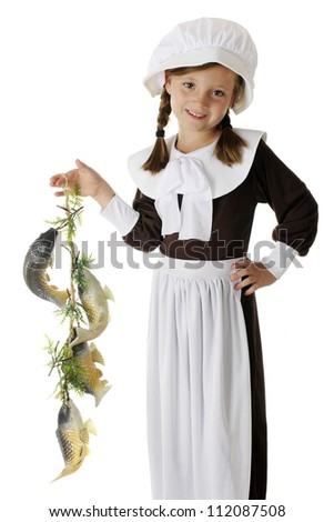 A beautiful, elementary Pilgrim girl happily displaying the colony's catch of fish, a likely food for the first Thanksgiving feast.  On a white background. - stock photo