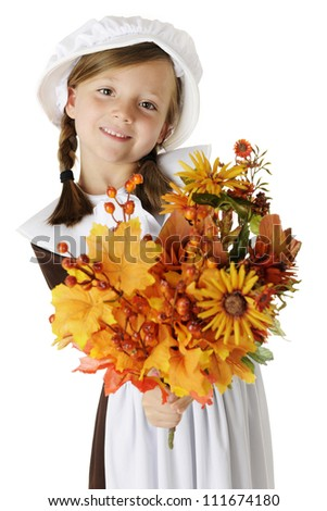 """A beautiful elementary """"pilgrim"""" girl happily holding out a bouquet of autumn flowers, leaves and berries for the viewer.  On a white background. - stock photo"""