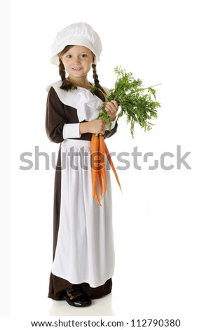 A beautiful elementary Pilgrim girl holding a bunch of fresh carrots.  On a white background. - stock photo