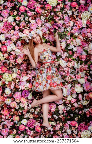 A beautiful emotional girl with flowers bouquet near a floral wall. - stock photo