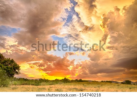 A beautiful epic sunset with blue sky behind the colorful majestic clouds. A scenic country landscape view looking west to the Colorado Rocky Mountains in Boulder County where the sky meets the land.  - stock photo