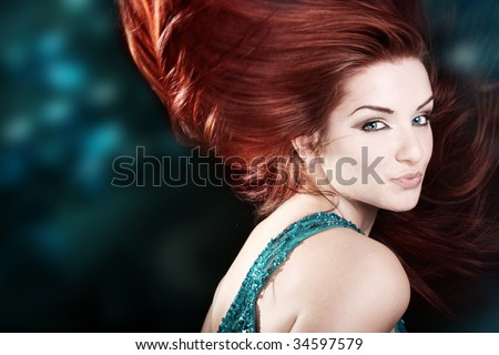 A beautiful fiery red haired woman with her hair mid movement with a blue abstract background.