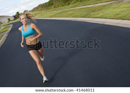 A beautiful fit and healthy blond woman road running while listening to music on her portable mp3 player - stock photo