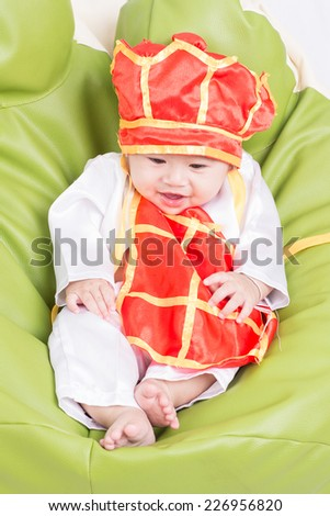A beautiful five month year old baby boy wearing a   buddhist monk - stock photo