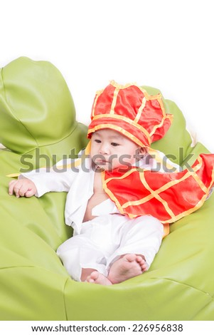 A beautiful five month year old baby boy wearing a   buddhist monk on white background. - stock photo