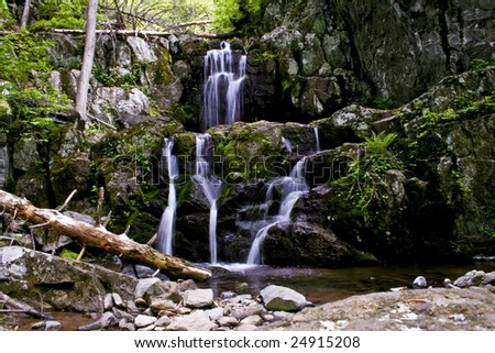 a beautiful flowing mountain waterfall in the forest - stock photo