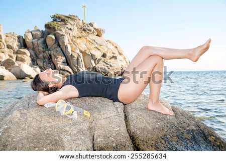 A beautiful freediver woman is relaxing on a rock