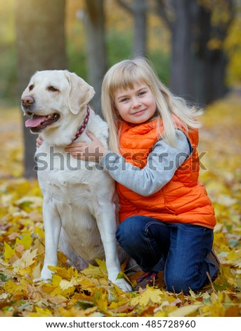 A beautiful girl and her dog Labrador retriever posing in autumn park. Yellow and orange leaves around.